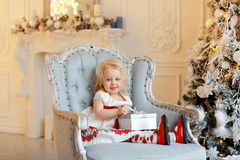 Little baby girl charming blonde, smiling and sitting in a chair Royalty Free Stock Image