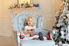 Little baby girl charming blonde, smiling and sitting in a chair Stock Photos