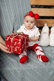 Little baby girl with Christmas present on bench with knitted blanket. stock photography