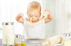 Little baby girl is cooking, kneads dough baking Stock Image
