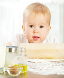 Little baby girl is cooking, kneads dough baking Royalty Free Stock Images