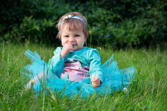 Little baby girl crawling on grass outdoors Stock Photo