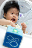 Little baby girl crying on a high chair Stock Photo