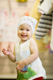 The little baby girl dancing in clothes store Stock Photo