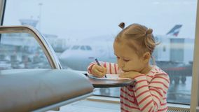 Little baby girl drawing at airport with plane on the background. Child waiting flight at departure lounge Royalty Free Stock Images