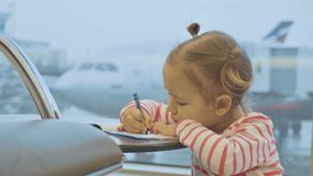 Little baby girl drawing at airport with plane on the background. Child waiting flight at departure lounge Stock Photo
