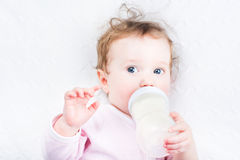 Little baby girl drinking milk out of a bottle Stock Image