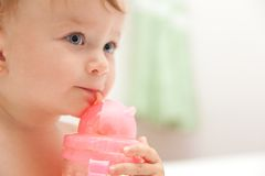 Little baby girl drinks juice from a bottle Stock Photography