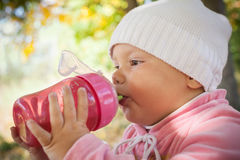 Little baby girl drinks from pink plastic bottle. Little baby girl in autumn park drinks from pink plastic bottle Royalty Free Stock Photography