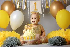 Little baby girl eating birthday cake during cake smash party stock photos