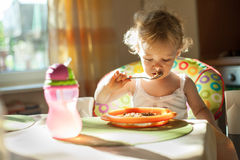 Little baby girl eating breakfast Stock Images