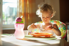 Little baby girl eating breakfast Royalty Free Stock Image