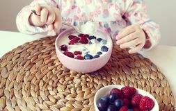 Little baby girl eating healthy breakfast at home, berries and yogurt. Little baby girl eating healthy breakfast at home, yogurt and berries, spring, summer Royalty Free Stock Photography