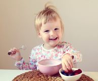 Little baby girl eating healthy breakfast at home, berries and yogurt Stock Photos