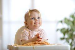 Little baby girl eating pasta Stock Photo