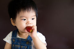 Little baby girl eating strawberry Stock Photo