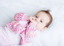 Little baby girl enjoying tummy time in a pink cardigan Stock Photos