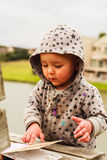 A little baby girl examines a book. Vertical photo, photo took in New Zealand, girl is 19 month royalty free stock images