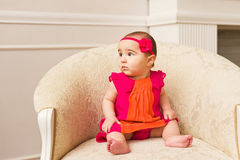 Little baby girl - face closeup. Arabic kid. Baby girl on white sofa Royalty Free Stock Images