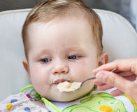Little baby girl feeding with a spoon Royalty Free Stock Photos