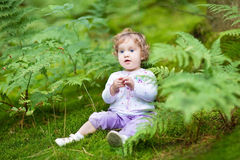 Little baby girl gathering wild raspberries in park Stock Photo