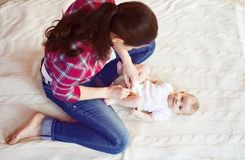 Little baby girl getting dressed by her mother Royalty Free Stock Photography