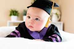 Baby girl in graduation cap and gown Stock Images