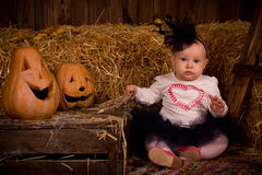 Little baby girl on Halloween party with pumpkin Royalty Free Stock Images