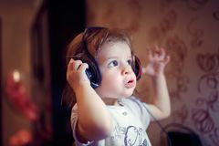 Home, technology and music concept - little girl with headphones at home. Little baby girl with headphones listen music emotionally at home royalty free stock photos