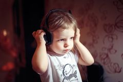 Home, technology and music concept - little girl with headphones at home. Little baby girl with headphones listen music emotionally at home stock image