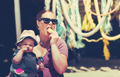 Little baby girl with her mother on the beach eating ice Royalty Free Stock Photo