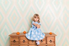 A little baby girl in her room sitting cross-legged on chest of drawers with tangerines on the rhomb wallpaper stock image