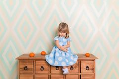 A little baby girl in her room sitting cross-legged on chest of drawers with tangerines on the rhomb wallpaper. Background. Child in blue polka dot dress and stock photo