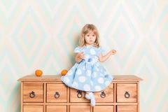 A little baby girl in her room sitting cross-legged on chest of drawers with tangerines on the rhomb wallpaper. Background. Child in blue polka dot dress and royalty free stock photos