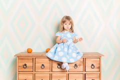 A little baby girl in her room sitting cross-legged on chest of drawers with tangerines on the rhomb wallpaper. Background. Child in blue polka dot dress and stock images