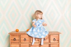 A little baby girl in her room sitting cross-legged on chest of drawers with tangerines on the rhomb wallpaper royalty free stock image
