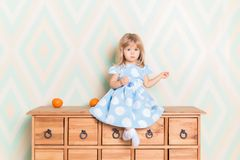 A little baby girl in her room sitting cross-legged on chest of drawers with tangerines on the rhomb wallpaper. Background. Child in blue polka dot dress and royalty free stock photo