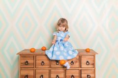 Little baby girl in her room sitting cross-legged on chest of drawers and throws tangerines down on rhomb wallpaper. Background. Child in blue polka dot dress stock image