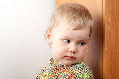 Little baby girl hiding behind a cupboard Royalty Free Stock Image