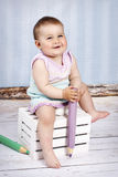 Little baby girl holding big crayon Royalty Free Stock Images