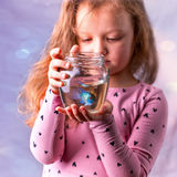 Little baby girl holding a fishbowl with a blue fish. Care conce Stock Photos