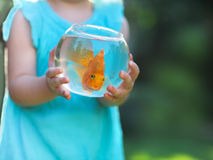 Little baby girl holding a fishbowl with a goldfish on a nature Stock Photo