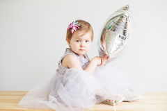 Little baby girl holding silver star-shaped balloon. Royalty Free Stock Photo