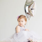 Little baby girl holding silver star-shaped balloon. Royalty Free Stock Image