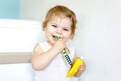 Little baby girl holding toothbrush and brushing first teeth. Toddler learning to clean milk tooth. Royalty Free Stock Photography