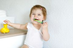 Little baby girl holding toothbrush and brushing first teeth. Toddler learning to clean milk tooth. Prevention, hygiene and healthcare concept. Happy child in royalty free stock image
