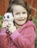 Little Baby Girl Holding Stuffed Toys Wearing Pink. Young brown haired little child girl with pretty blue eyes holding favorite toys and smiling on a brisk Royalty Free Stock Photography