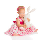 Little baby girl hugging a  toy bunny rabbit  on white. Background Stock Photos