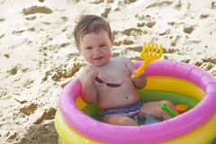Little baby girl in the inflatable swimming pool. Portrait of cute little baby girl in the inflatable swimming pool with pink sunglasses stock images