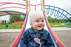 Little baby girl in jeans and a cap down from a hill on the playground with swings Stock Image
